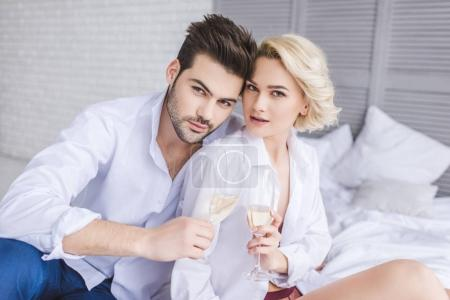 beautiful young couple in white shirts holding glasses of champagne and looking at camera