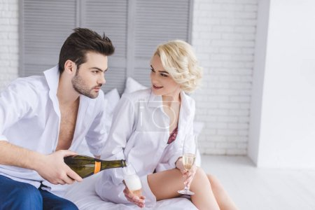 young couple looking at each other while drinking champagne on bed