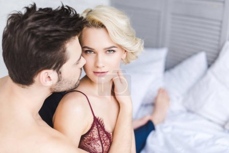 Photo for Sexy blonde woman in lingerie looking at camera while hugging with boyfriend on bed - Royalty Free Image