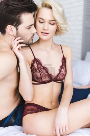 Photo for Sexy young woman in lingerie touching handsome boyfriend on bed - Royalty Free Image