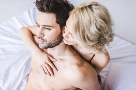 high angle view of beautiful sensual couple hugging on bed