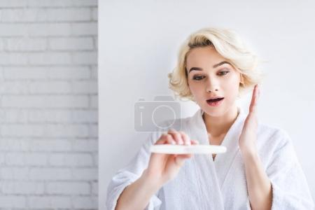 surprised young woman in bathrobe holding pregnancy test