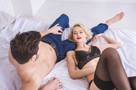 Photo pour Sexy jeune couple regardant l'autre tout en étant couché ensemble sur le lit - image libre de droit