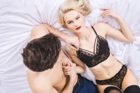top view of sexy young woman looking at camera while lying with boyfriend in bed