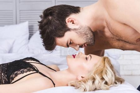 side view of beautiful young couple able to kiss in bed