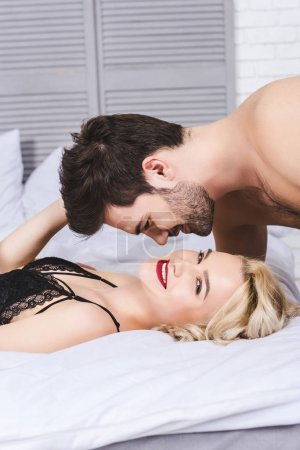 beautiful young couple able to kiss in bed