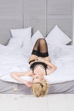 Photo pour Séduisante jeune femme en lingerie dentelle, couché sur le lit avec verre de champagne à l'étage - image libre de droit