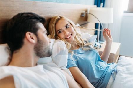 Photo pour Couple souriant se regardant dans le lit - image libre de droit