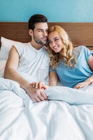 heterosexual couple holding hands in bed