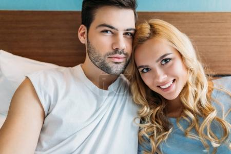 affectionate heterosexual couple looking at camera in bed