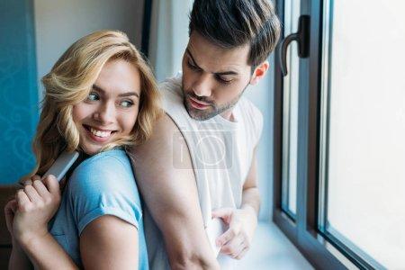 Foto de Sonriente pareja oculta smartphones de uno a - Imagen libre de derechos