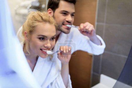 Photo pour Couple affectueux se brosser les dents et en regardant de miroir - image libre de droit