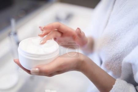 cropped image of girl taking cream in bathroom
