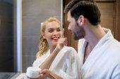 smiling girlfriend applying cream on boyfriend face