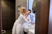 boyfriend looking how girlfriend applying cream on face