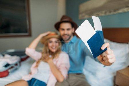 Photo pour Couple souriant dans la chambre d'hôtel avec passeports avec billets au premier plan - image libre de droit