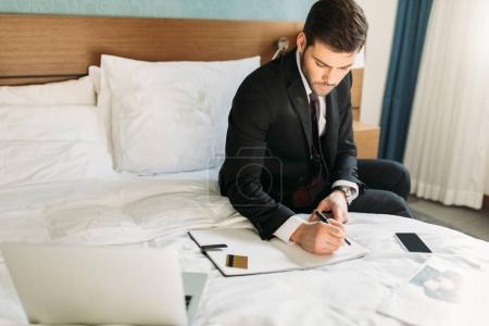 businessman writing something to notebook while sitting on bed in hotel room