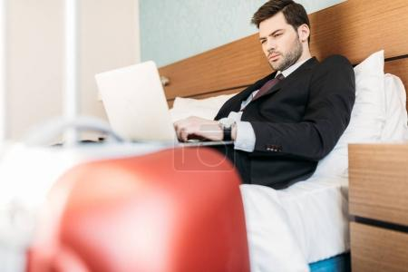 businessman lying on bed in hotel room and using laptop