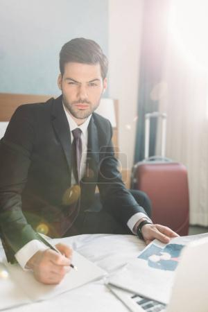 businessman sitting on bed with newspaper and notebook