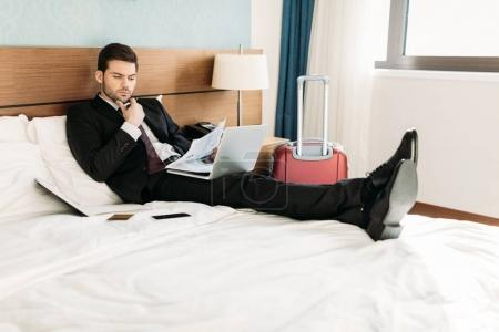 Foto de Empresario de mentira en cama en habitación de hotel y leyendo periódico - Imagen libre de derechos