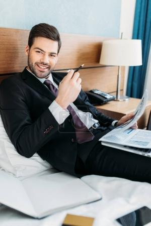 happy businessman holding newspaper and looking at camera