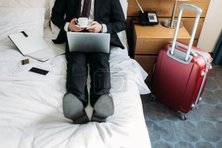 Foto de Recortar imagen de empresario acostado en cama de hotel con café y portátil - Imagen libre de derechos