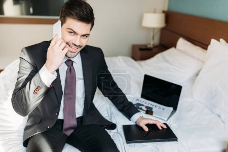 smiling businessman talking by smartphone and sitting on bed in hotel room