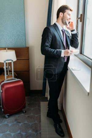 handsome businessman talking by smartphone in hotel room and looking at window
