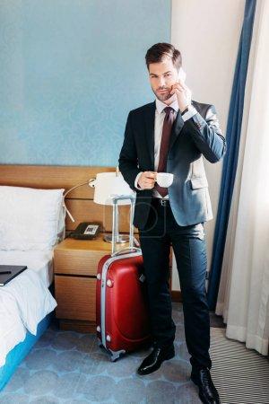 Foto de Apuesto hombre de negocios hablando por teléfono inteligente en habitación de hotel - Imagen libre de derechos