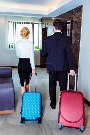 rear view of businessman and businesswoman walking with luggage to hotel elevator