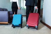 cropped image of businessman and businesswoman walking with luggage to hotel elevator