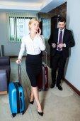 beautiful businesswoman talking by smartphone in hotel corridor