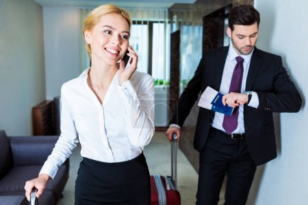 smiling businesswoman talking by smartphone in hotel corridor