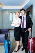 businessman and businesswoman with passports and tickets in hotel corridor