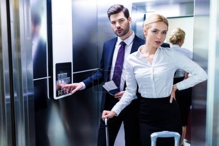 Foto de Empresario y empresaria en el ascensor mirando a cámara - Imagen libre de derechos
