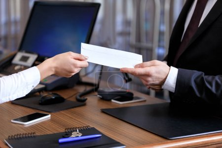 cropped image of receptionist giving envelope to businessman in hotel