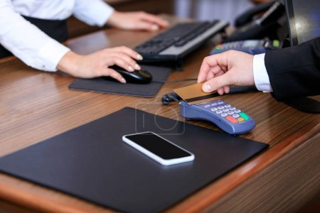 cropped image of businessman paying with credit card at reception desk in hotel