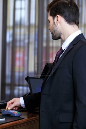 side view of businessman paying with credit card in hotel