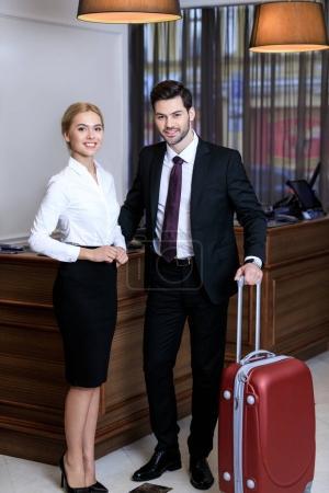 Foto de Feliz hombre de negocios y empresaria cerca de recepción en hotel - Imagen libre de derechos