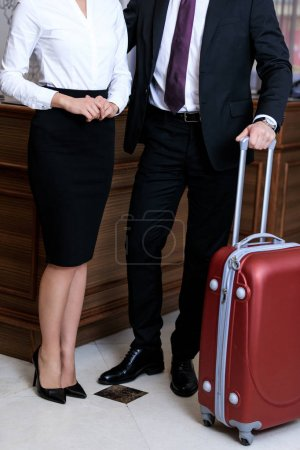 cropped image of businessman and businesswoman standing at reception desk in hotel
