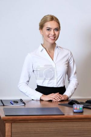 smiling attractive receptionist standing at reception desk in hotel