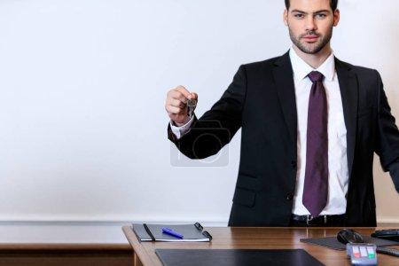 handsome receptionist holding key at reception desk