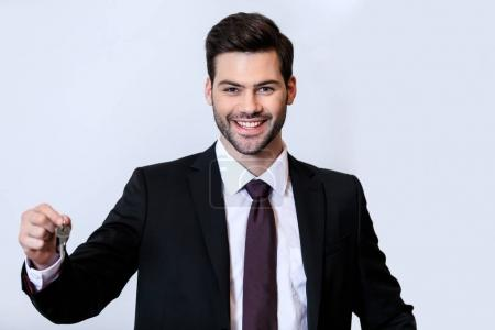 smiling handsome receptionist holding key isolated on white