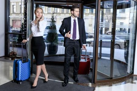 businesswoman talking by smartphone and businessman looking away