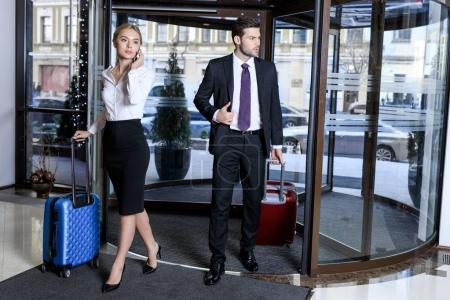 Foto de Mujer de negocios hablando por teléfono inteligente y hombre de negocios mirando lejos - Imagen libre de derechos