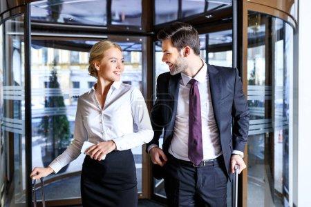 Foto de Sonriente hombre de negocios y empresaria entrar en hotel y mirando el uno al otro - Imagen libre de derechos