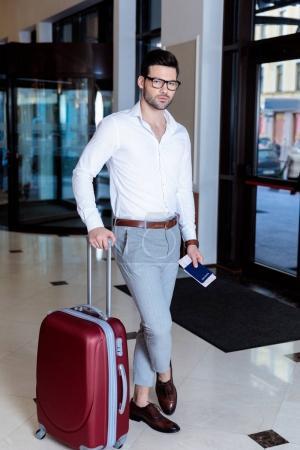 beau touriste avec sac de voyage et passeport en regardant la caméra