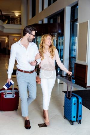 couple of travelers walking with travel bags in hotel