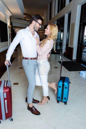 Photo pour Heureux couple de voyageurs hugging en hôtel et en regardant l'autre - image libre de droit