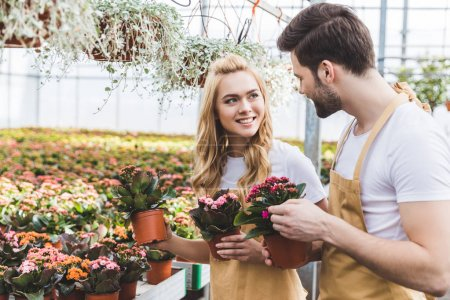 Smiling gardeners holding pots with flowers in greenhouse